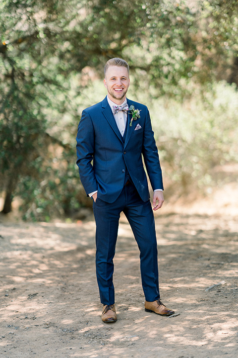 Circle-Oak-ranch-wedding-groom-standing-in-a-cobalt-suit-with-a-floral-bowtie