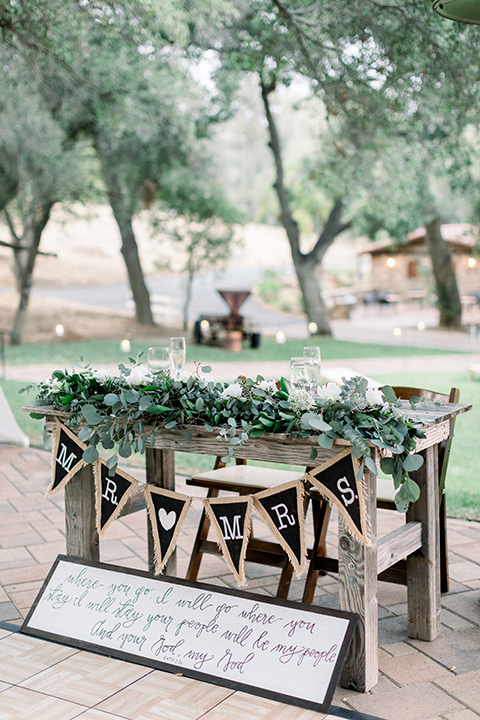 Circle-Oak-ranch-wedding-sweetheart-table-with-a-wooden-table-and-chair-with-greenery-draped-on-it