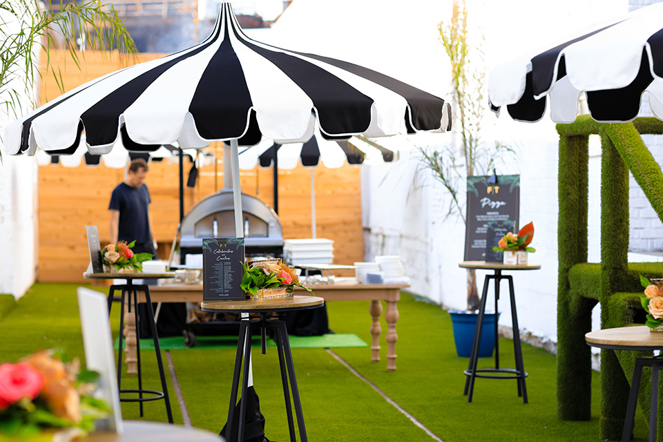 Friar-Tux-Summer-Bash-bar-outdoor-space-with-green-astro-turf-everywhere-and-modern-black-and-white-umbrellas