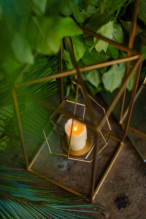 candle decor in wire casing with surrounded by greenery