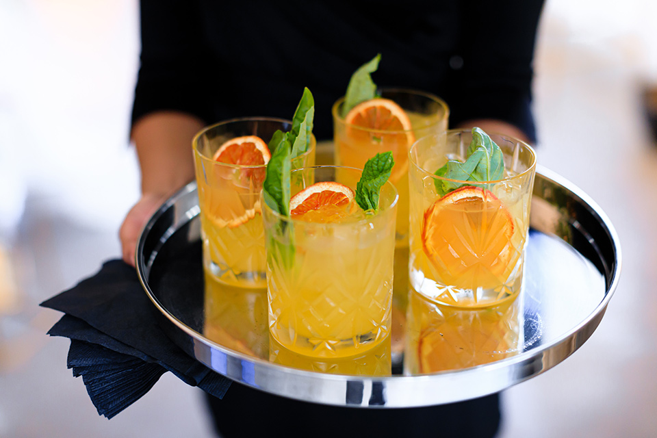 Yellow decorated cocktails with garnish and orange peel served on a platter