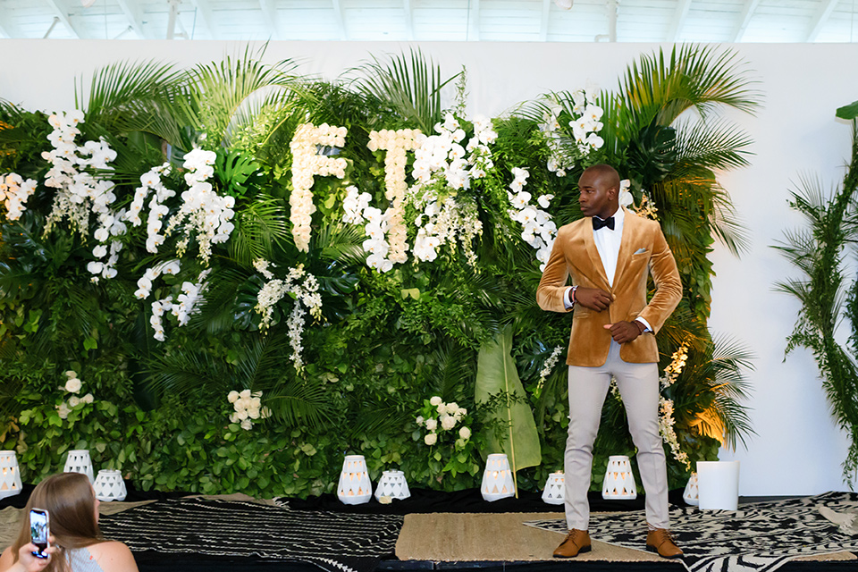 Friar Tux summer Bash model standing on velvet carpet in front of florals