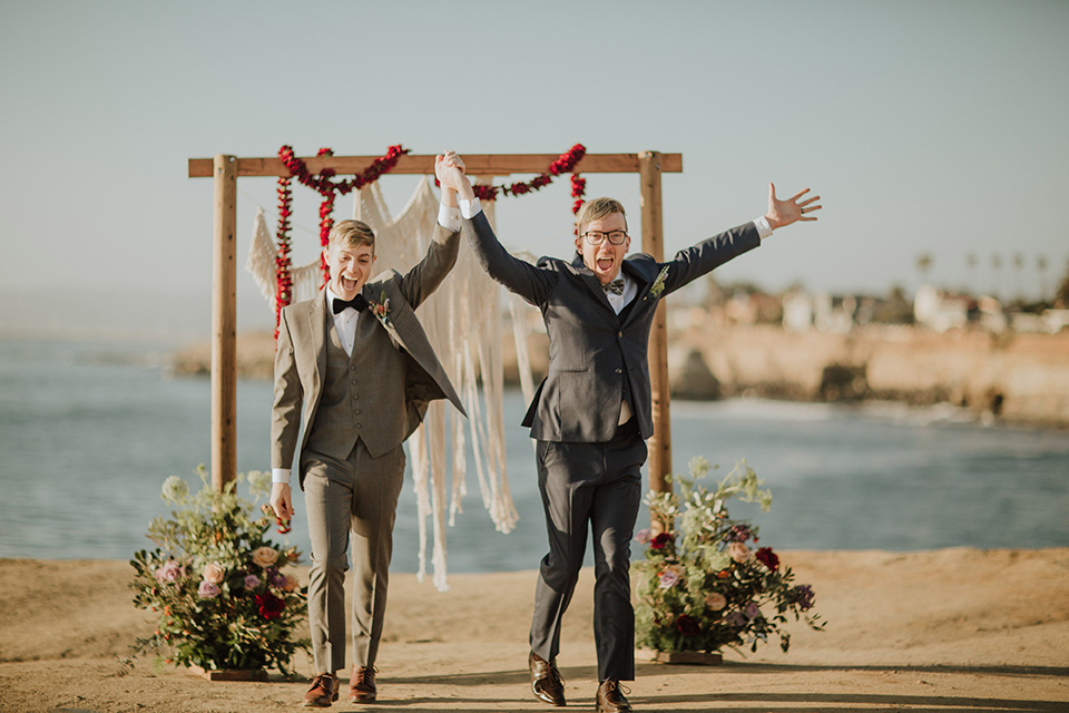 Sunset-Cliffs-Shoot-grooms-at-ceremony-space-one-groom-in-a-grey-suit-with-the-other-groom-in-a-blue-suit-over-looking-the-ocean-with-a-wooden-arch-and-hanging-flowers