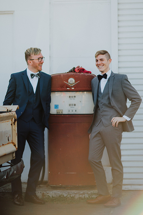 Sunset-Cliffs-Shoot-grooms-by-gas-pump-one-groom-in-a-grey-suit-and-the-other-groom-in-a-blue-suit