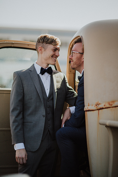 Sunset-Cliffs-Shoot-grooms-in-truck-one-groom-in-a-grey-suit-and-one-groom-in-a-navy-suit