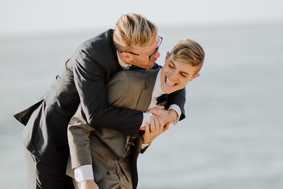 Sunset-Cliffs-Shoot-grooms-laughing-one-groom-in-a-grey-suit-with-the-other-groom-in-a-blue-suit
