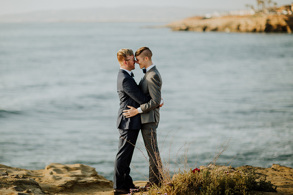 Sunset-Cliffs-Shoot-grooms-overlooking-ocean-one-groom-in-a-grey-suit-with-the-other-groom-in-a-blue-suit