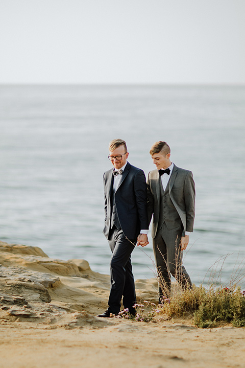 Sunset-Cliffs-Shoot-grooms-walking-by-cliff-one-groom-in-a-grey-suit-and-one-groom-in-a-navy-suit