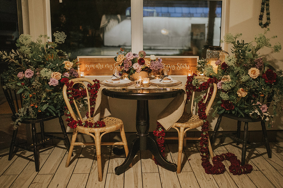 Sunset-Cliffs-Shoot-table-set-up-with-wooden-chairs-and-gold-decor