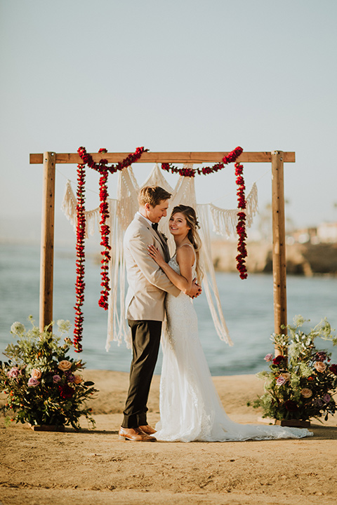 Sunset-Cliffs-Elopement-bride-and0-groom-kiss-at-ceremony-bride-in-a-lace-white-gown-with-thin-straps-groom-in-a-tan-suit-coat-with-black-pants-and-black-bow-tie