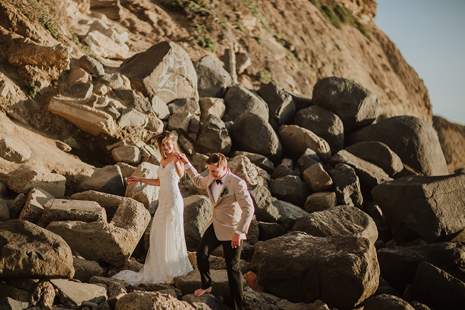 Sunset-Cliffs-Elopement-bride-and-groom-at-rocks-bride-in-a-lace-form-fitting-gown-with-thin-straps-groom-in-a-tan-suit-coat-with-black-pants-and-black-bow-tie
