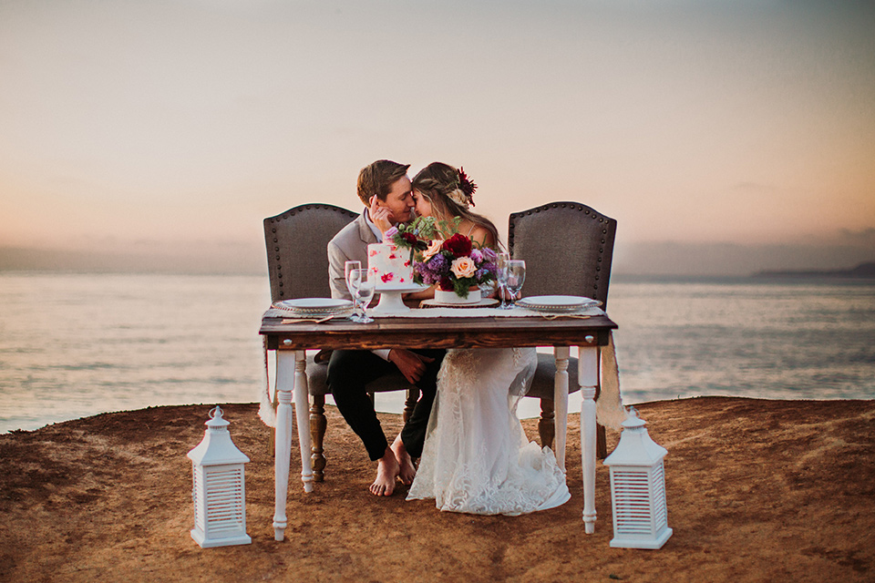 Sunset-Cliffs-Elopement-bride-and-groom-at-sweetheart-table-bride-in-a-lace-form-fitting-gown-with-thin-straps-groom-in-a-tan-suit-coat-with-black-pants-and-black-bow-tie