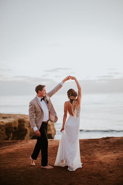 Sunset-Cliffs-Elopement-bride-and-groom-dancing-bride-in-a-lace-white-gown-with-thin-straps-groom-in-a-tan-suit-coat-with-black-pants-and-black-bow-tie