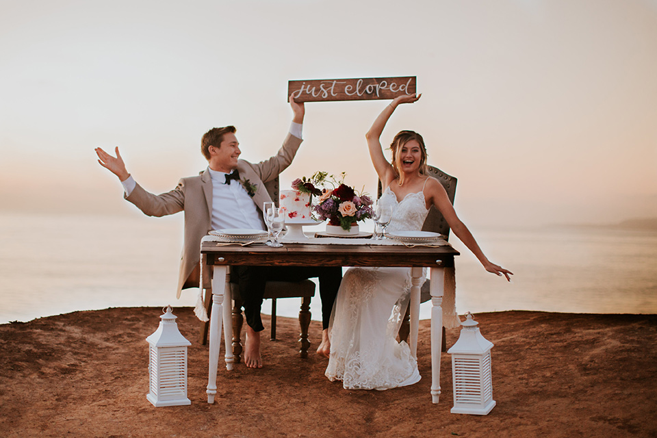 Sunset-Cliffs-Elopement-bride-and-groom-holding-up-elopement-sign-bride-in-a-lace-form-fitting-gown-with-thin-straps-groom-in-a-tan-suit-coat-with-black-pants-and-black-bow-tie