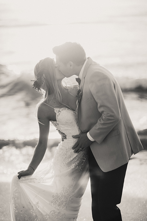 Sunset-Cliffs-Elopement-bride-and-groom-kissing-by-water-bride-in-a-lace-white-gown-with-thin-straps-groom-in-a-tan-suit-coat-with-black-pants-and-black-bow-tie