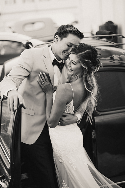 Sunset-Cliffs-Elopement-bride-and-groom-laughing-bride-in-a-lace-white-gown-with-thin-straps-groom-in-a-tan-suit-coat-with-black-pants-and-black-bow-tie