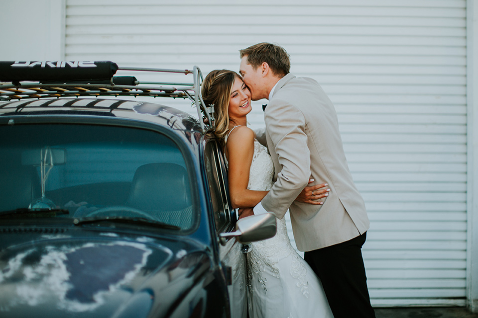 Sunset-Cliffs-Elopement-bride-and-groom-leaning-against-car-bride-in-a-lace-form-fitting-gown-with-thin-straps-groom-in-a-tan-suit-coat-with-black-pants-and-black-bow-tie