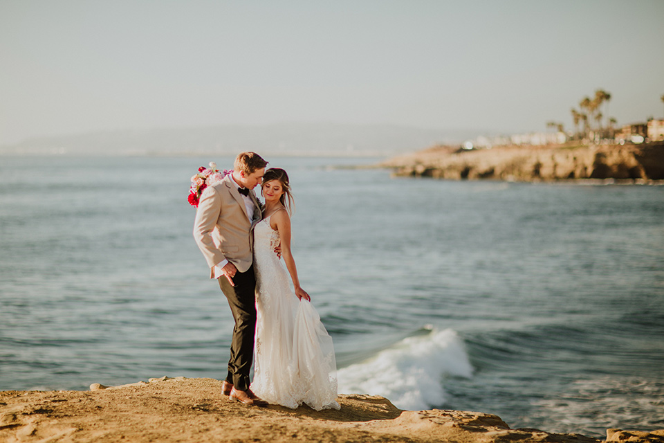 Sunset-Cliffs-Elopement-bride-and-groom-overlooking-cliffs-bride-in-a-lace-form-fitting-gown-with-thin-straps-groom-in-a-tan-suit-coat-with-black-pants-and-black-bow-tie