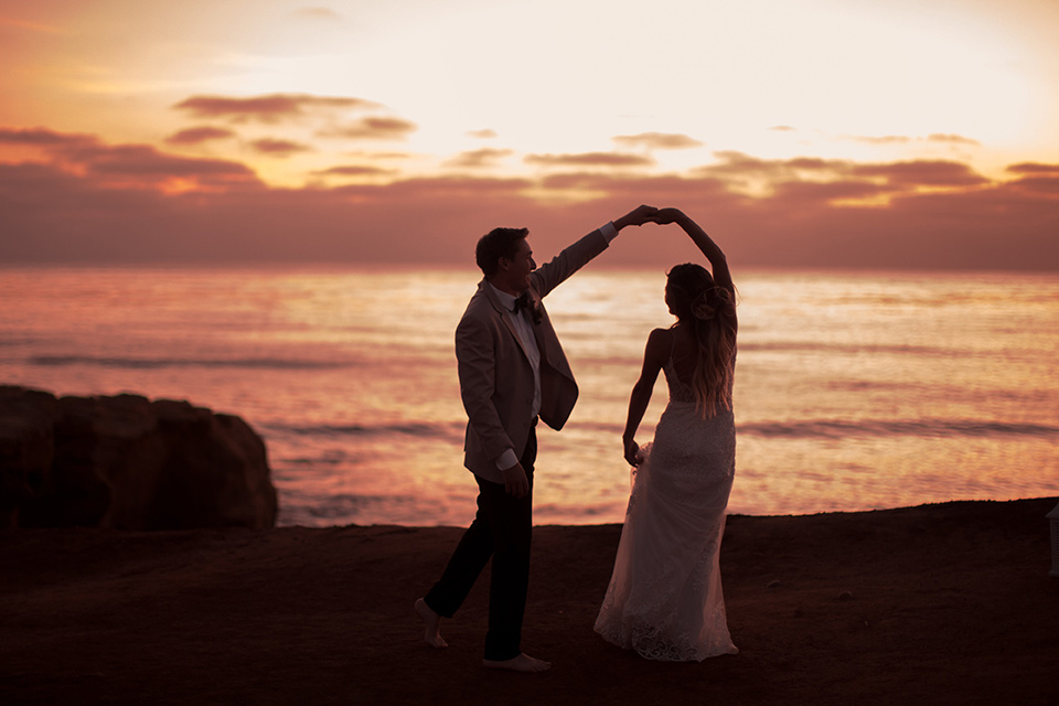Sunset-Cliffs-Elopement-bride-and-groom-twirling-at-sunset-bride-in-a-lace-form-fitting-gown-with-thin-straps-groom-in-a-tan-suit-coat-with-black-pants-and-black-bow-tie