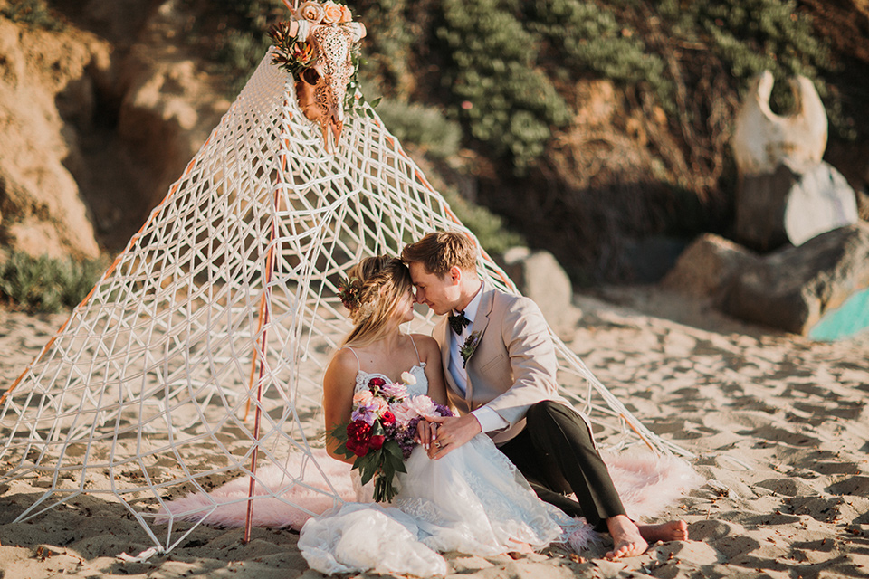 Sunset-Cliffs-Elopement-bride-and-groom-under-tent-bride-in-a-lace-form-fitting-gown-with-thin-straps-groom-in-a-tan-suit-coat-with-black-pants-and-black-bow-tie