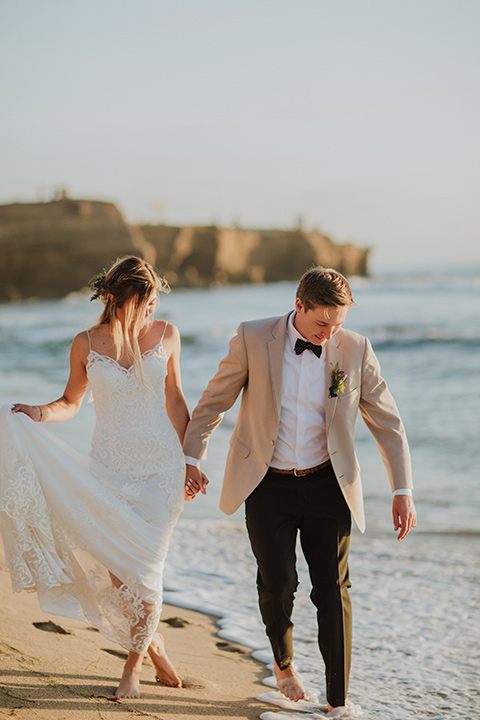 Sunset-Cliffs-Elopement-bride-and-groom-walking-by-water-bride-in-a-lace-white-gown-with-thin-straps-groom-in-a-tan-suit-coat-with-black-pants-and-black-bow-tie