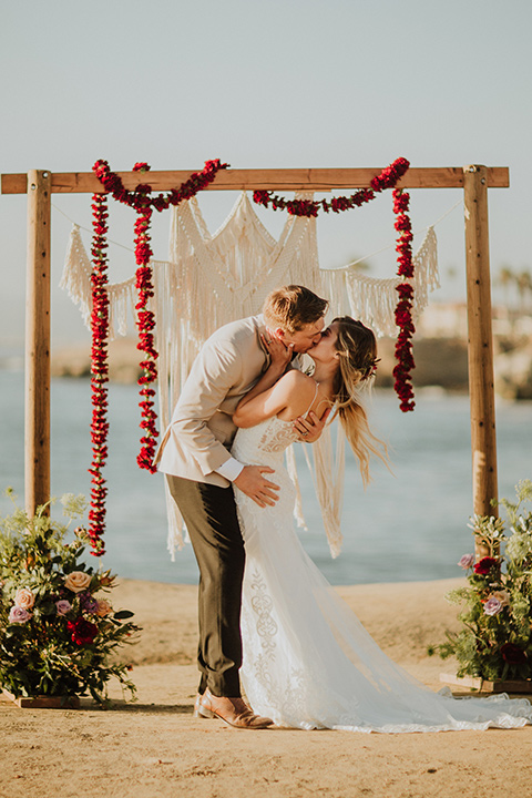 Sunset-Cliffs-Elopement-bride-and-groom-kiss-at-ceremony-bride-in-a-lace-white-gown-with-thin-straps-groom-in-a-tan-suit-coat-with-black-pants-and-black-bow-tie