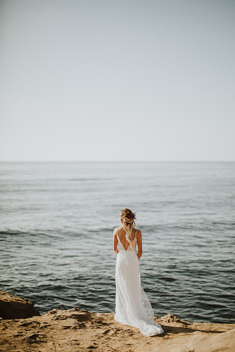 Sunset-Cliffs-Elopement-bride-looking-at-ocean-in-a-lace-white-gown-with-thin-straps