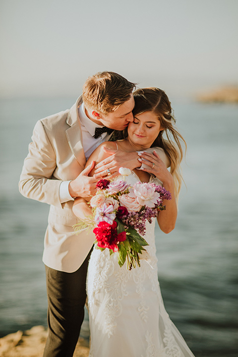 Sunset-Cliffs-Elopement-groom-hugging-bride-from-behind-bride-in-a-lace-white-gown-with-thin-straps-groom-in-a-tan-suit-coat-with-black-pants-and-black-bow-tie