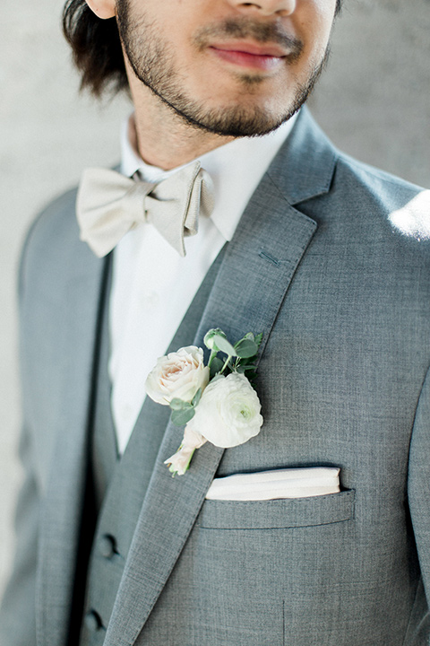 The-1912-Shoot-close-up-on-groom-suit-in-a-grey-suit-with-an-ivory-bow-tie