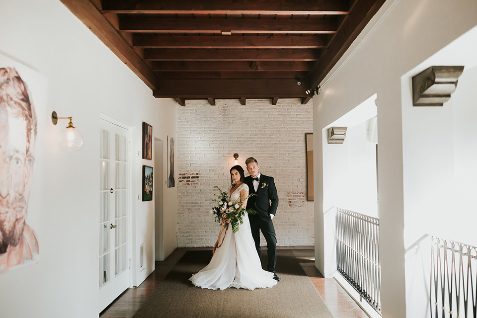 bride in a lace full gown with a cap sleeve and illusion neckline and the groom in a black suit with black long tie standing in hallway