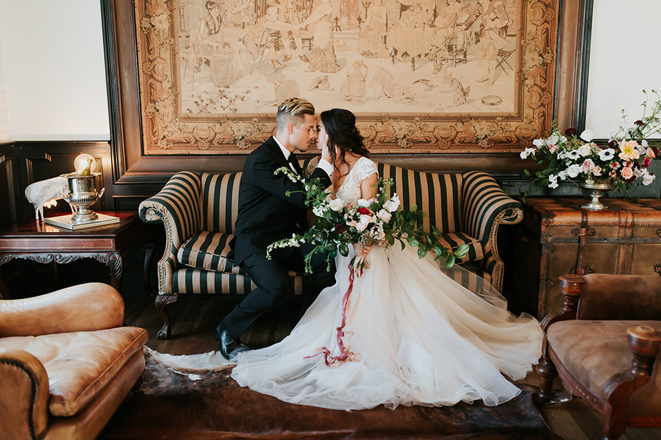 bride in a lace full gown with a cap sleeve and illusion neckline and the groom in a black suit with black long tie sitting on the couch