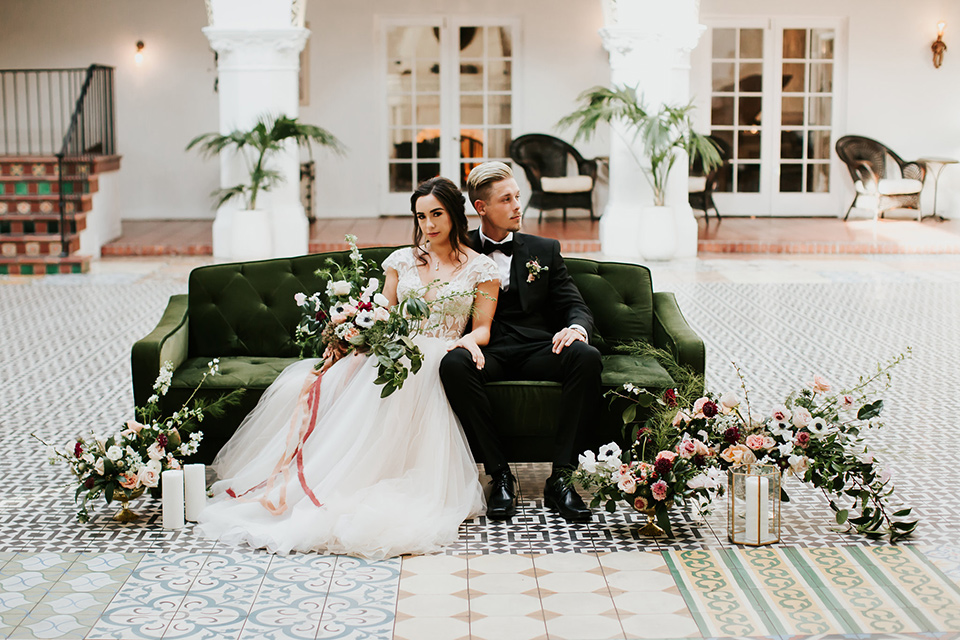 bride in a lace full gown with a cap sleeve and illusion neckline and the groom in a black suit with black long tie sitting on the couch outside