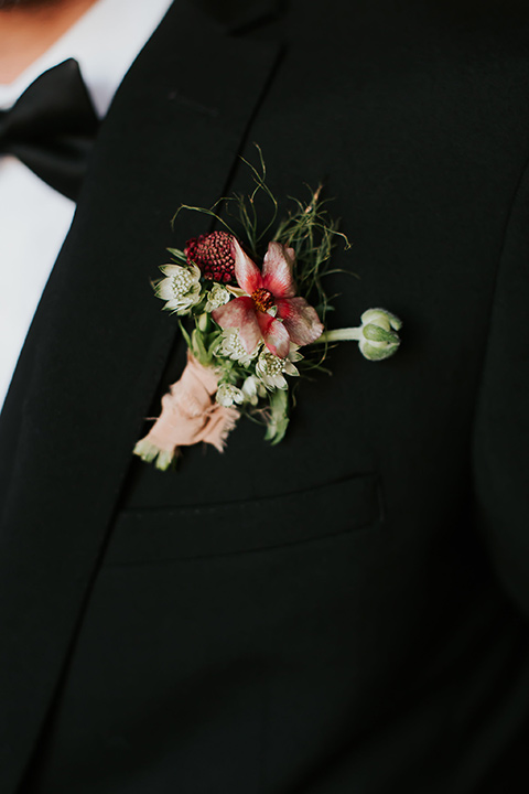 groom in a black suit with a long black tie close up