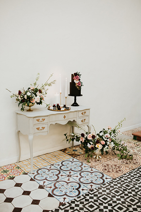 black cake with fun florals on a white vintage table