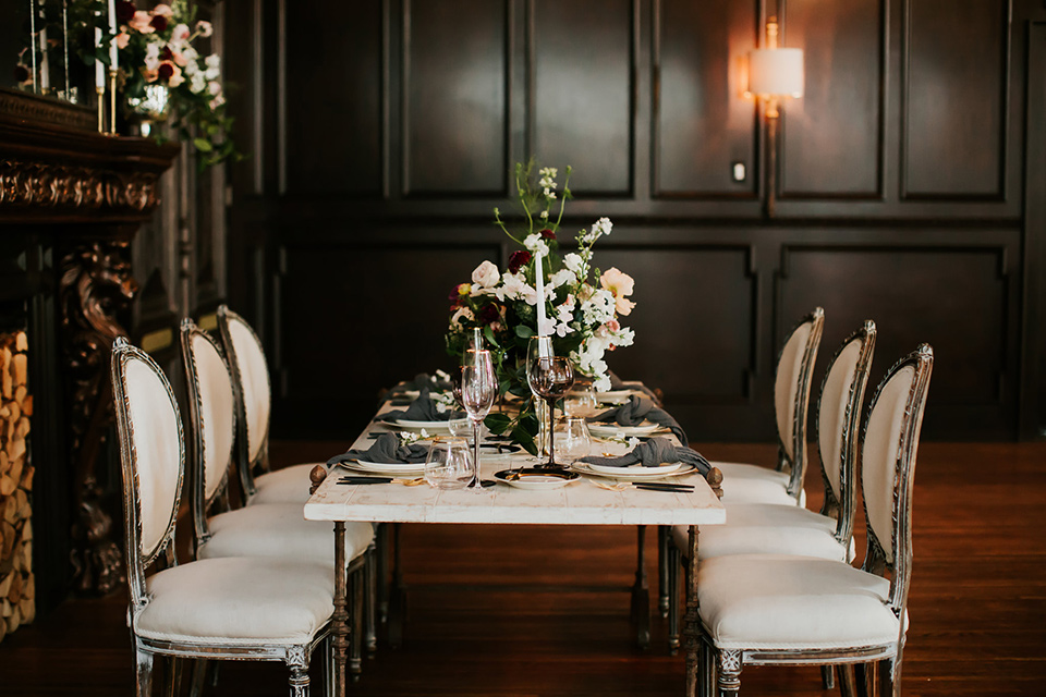 black table with white chairs and simple floral centerpiece design