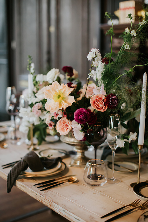 wooden tables with black candles and charger plates and white floral centerpiece