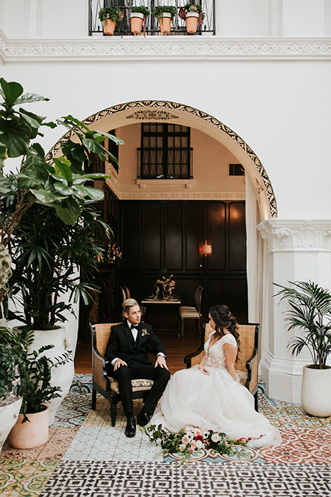 bride in a lace gown with a cap sleeve and the groom in a black suit with a black long tie sitting on chairs at the venue