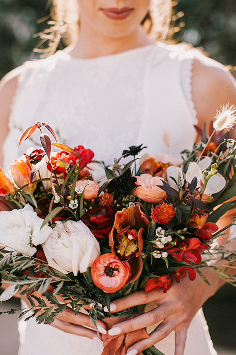 bride holding a fall inspired wedding bouquet with a white gown with a high neckline