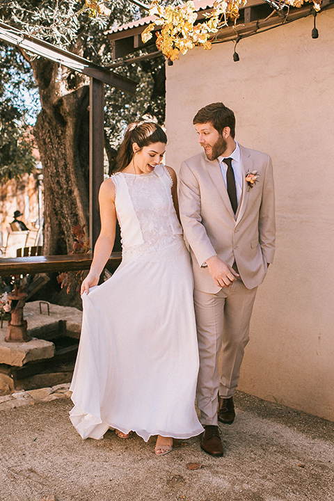 the bride in a white gown with a high neckline and sleeves, along with nude suede heels and her hair in a high ponytail the groom in a tan suit with a chocolate brown long tie