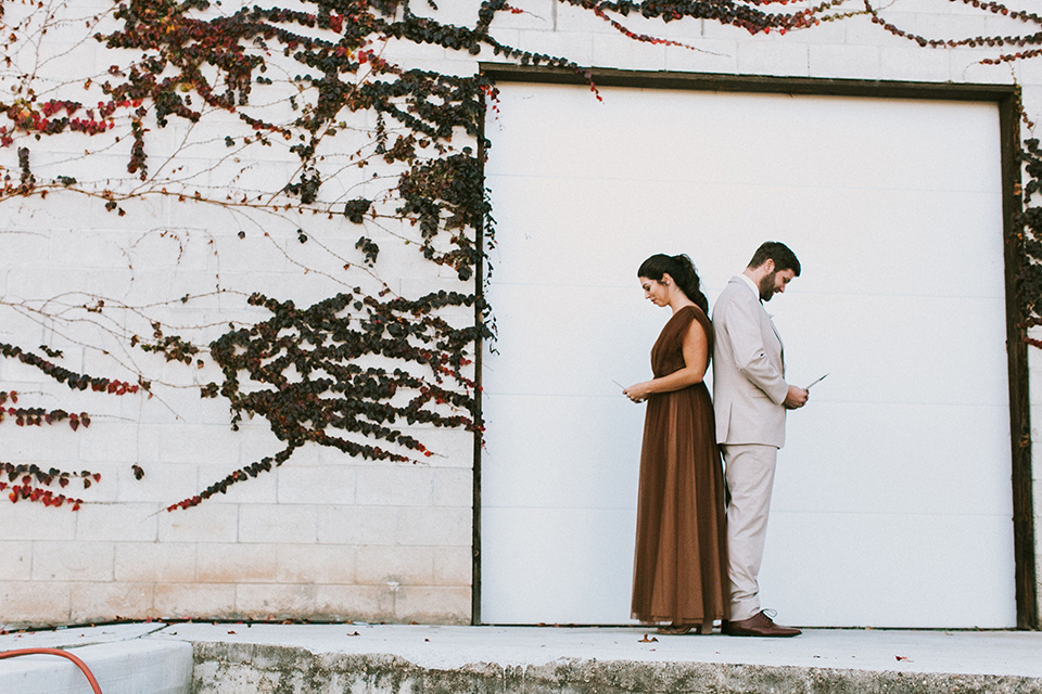 the bride in a chocolate and tan brown gown with a high neckline and sleeves, along with nude suede heels and her hair in a high ponytail and the groom in a tan suit with a chocolate brown long tie