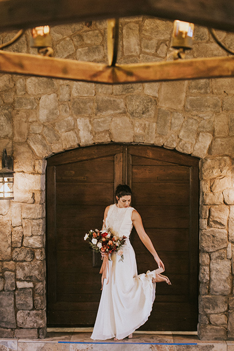 the bride in a white gown with a high neckline and sleeves, along with nude suede heels and her hair in a high ponytail