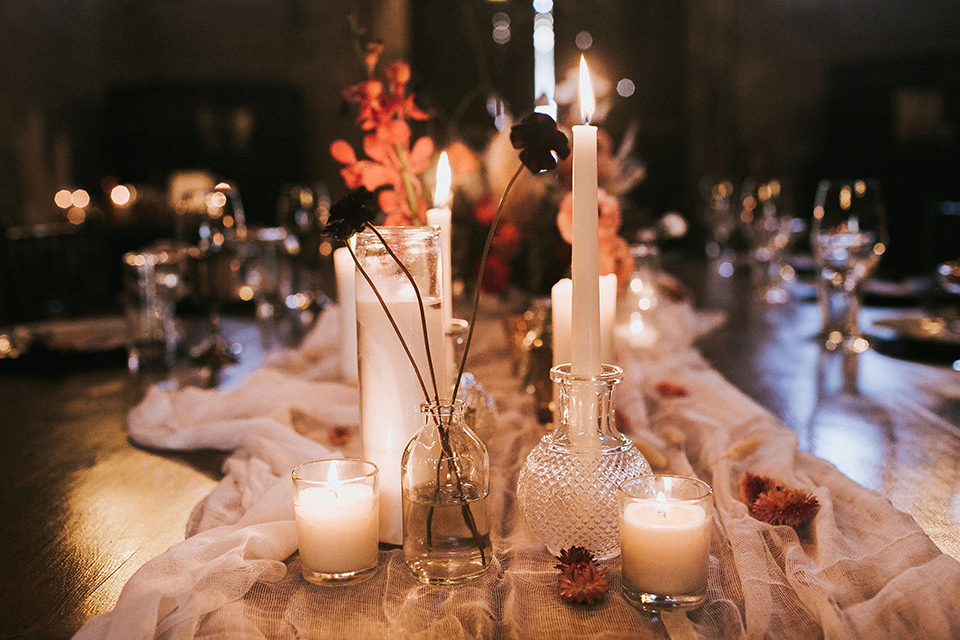wooden table with white linens and tall candles and orange and white accents
