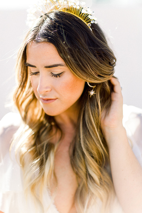Bride in a cream and ivory flowing gown with a gold headband with stars with her hair in waves