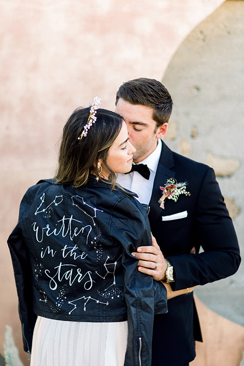 Bride in a cream and ivory flowing gown with a gold headband with stars and a jean jacket and the groom in a black tuxedo with a black bow tie