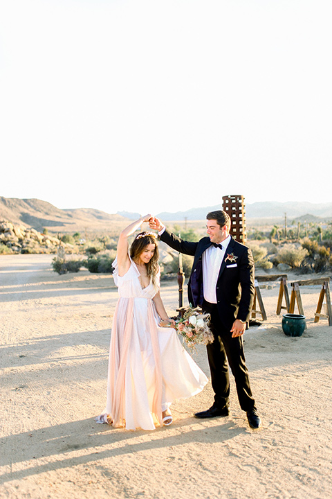 Bride in a cream and ivory flowing gown with a gold headband with stars and the groom in a black tuxedo with a black bow tie dancing