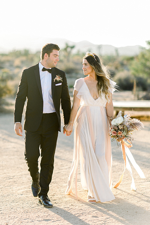 bride in a flowing ivory and rose gold style gown with a gold headband and the groom in a black tuxedo with a black bow tie