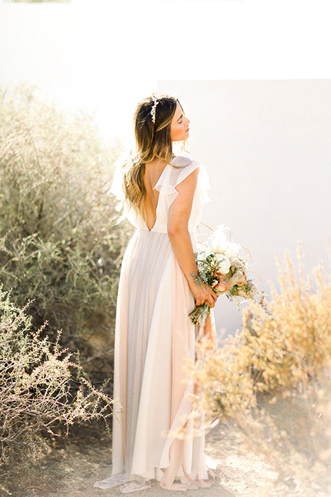 Bride in a cream and ivory flowing gown with a gold headband with stars