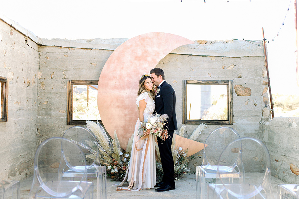 Bride in a cream and ivory flowing gown with a gold headband with stars and the groom in a black tuxedo with a black bow tie by a rose gold moon shaped arch at ceremony