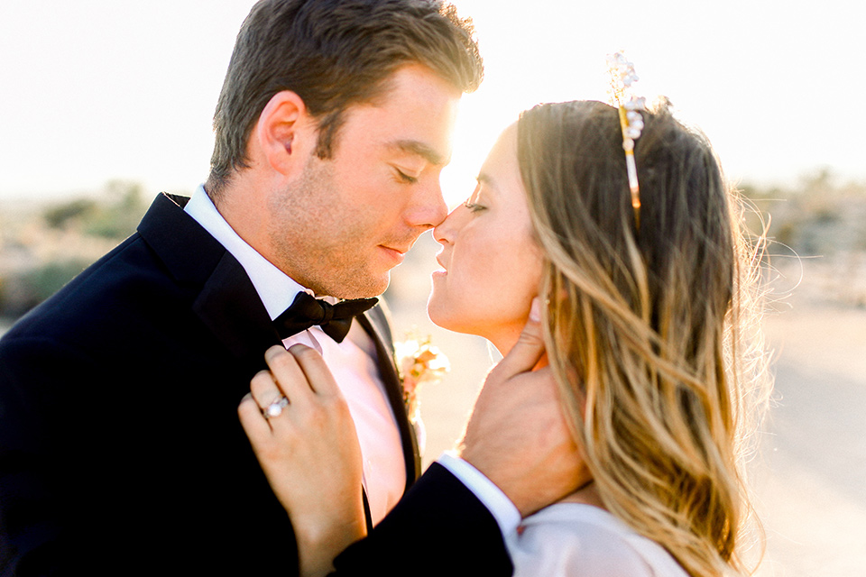 Bride in a cream and ivory flowing gown with a gold headband with stars and the groom in a black tuxedo with a black bow tie