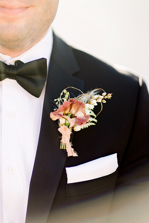 Black tuxedo with a black bow tie and a white and pink boutonnière